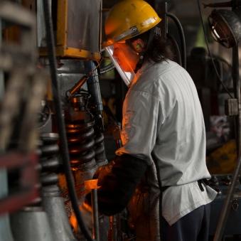 工場機械を操作する工員の画像