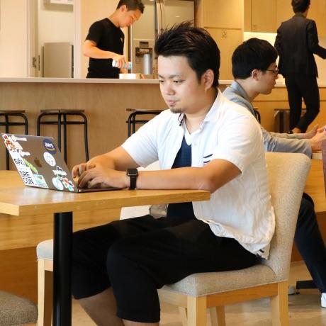 カフェでノートパソコンで作業する男性