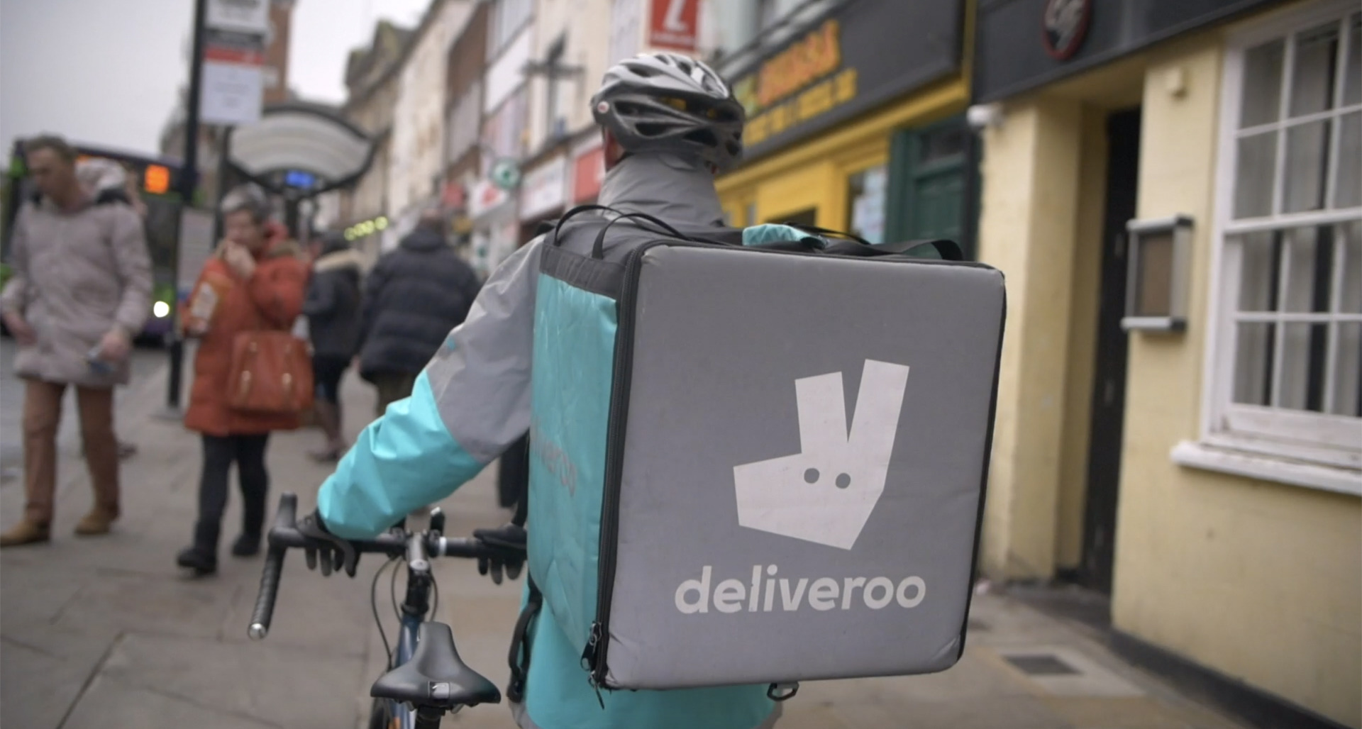 A Deliveroo cyclist on sidewalk with food delivery backpack.
