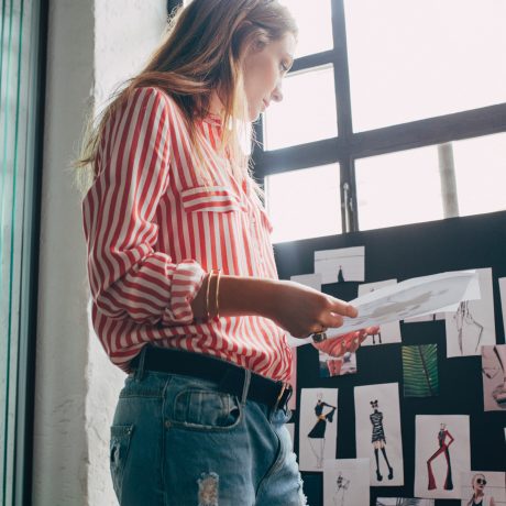A Hearst female employee looks at editorial fashion sketches.