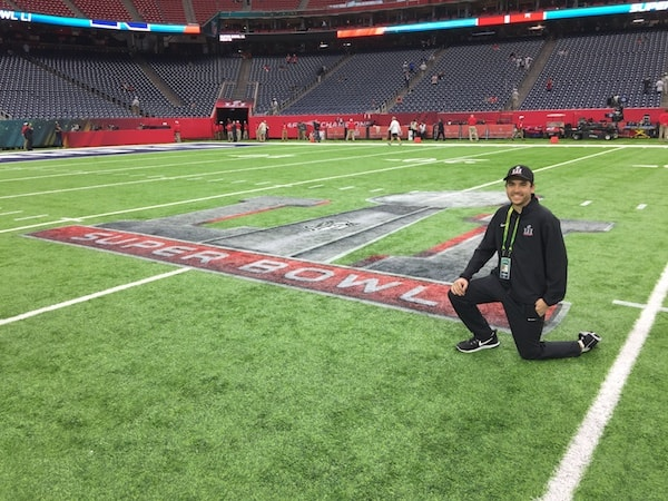McLaughlin poses in front of the Super Bowl Logo painted on the field of NRG Stadium