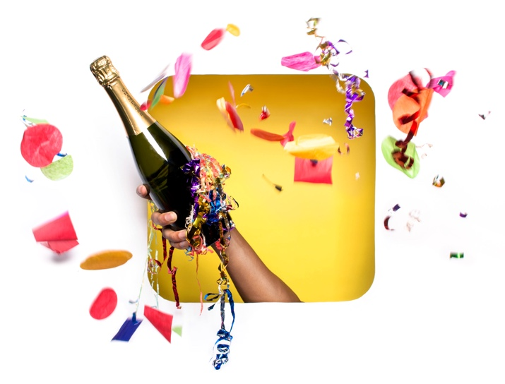 Celebratory image of sparkling beverage held out by an arm, surrounded by streamers and a pop of color.