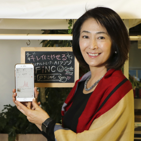 FiNC アプリをスマートフォンで紹介する人