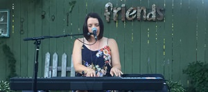 Shannon Curtis plays piano outdoors in a casual venue