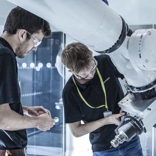 Two men inspecting a robotic arm