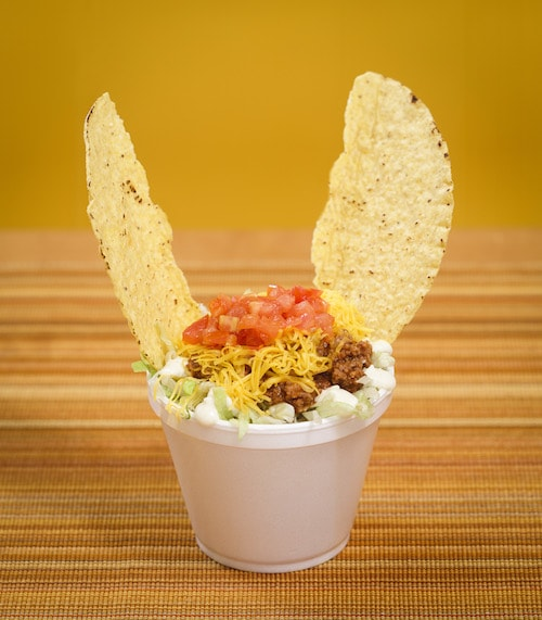 A short cup with Tex-Mex toppings on top and two chips pointing out like cat ears on top.