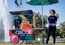 An Oscar Health employee standing in front of an Oscar Health cart full of merchandise