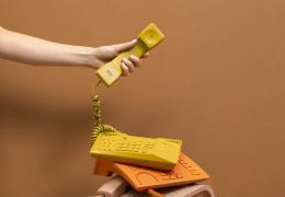Una mano sujetando el auricular de un teléfono amarillo