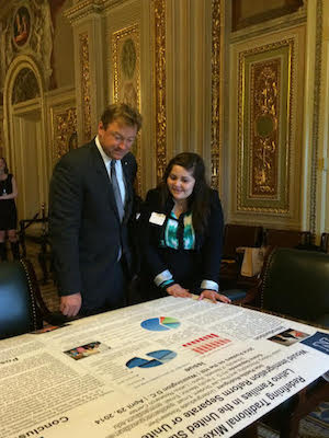Padilla-Rodríguez looks over a large research poster with Senator Dean Heller