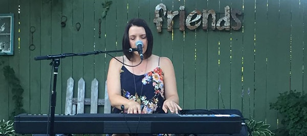 Shannon Curtis plays piano in a backyard.