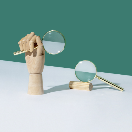 A wooden hand holding a magnifying glass figuratively represents SEEK, Australia's top job-search website.