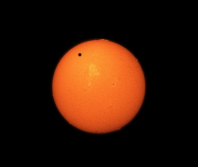 A small dot (Venus) crosses the top half of our glowing molting sun.