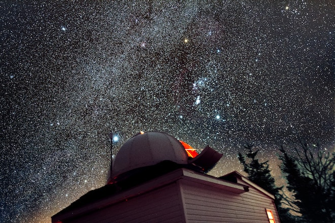 An observatory is in the foreground and millions of stars are visible in the background.