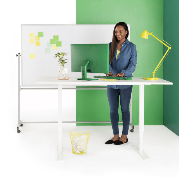 Smiling woman types on laptop while at standing desk.