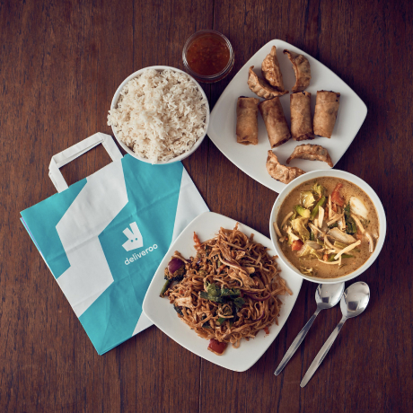 A deliveroo bag surrouded by food dishes