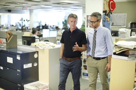 Two reporters in a busy and messy newsroom.
