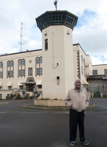 An older Frank Thompson wearing a track jacket stands outside near a penitentiary watch tower.