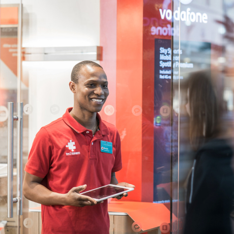 A Vodafone employee uses an iPad to assist a customer in a retail store.
