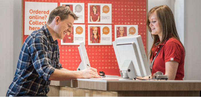 A Vodafone employee assists a customer at a retail store.