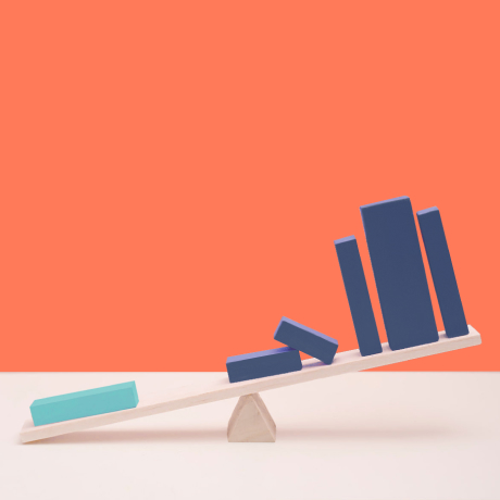 A seesaw with building blocks arranged as a bar graph illustrates HubSpot's focus on growth.