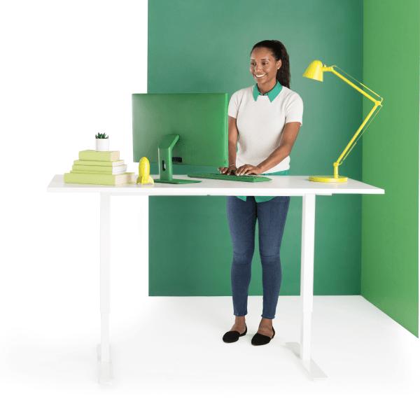 Una mujer sonriente que escribe en una computadora en un escritorio de pie.