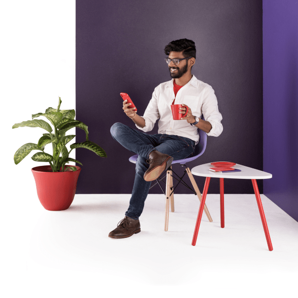 A man sits in a chair. He smiles warmly at the mobile phone in hand as coworkers post their status updates in Slack.