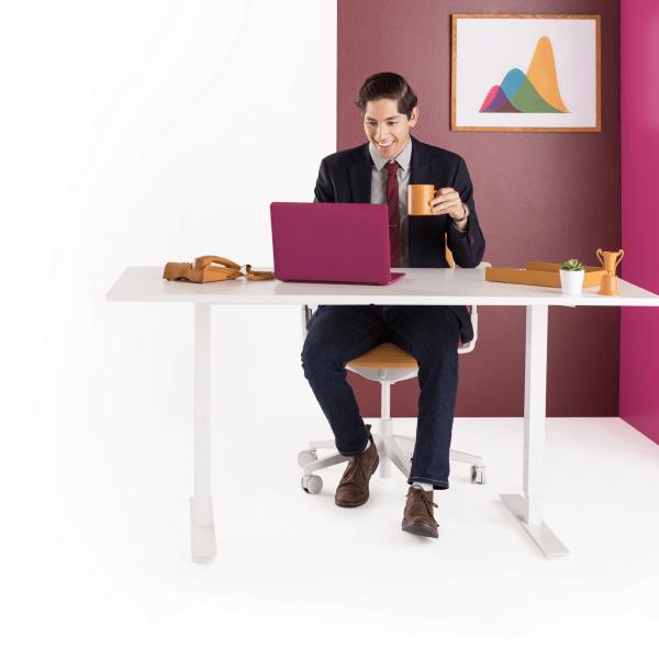 Un hombre sentado en un escritorio con su portátil cerrando acuerdos con su equipo y colaborando en Slack.
