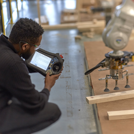 Worker observing machinery while using a handheld computer