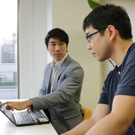 ノートパソコンを見ている会社員2人