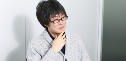 カーディガンを着た眼鏡の男性が椅子に座り、あごに手をあて考えながら話している。