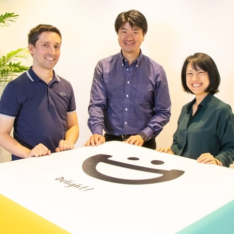 Three DeNA employees smiling and standing at a cubic table with the DeNA logo