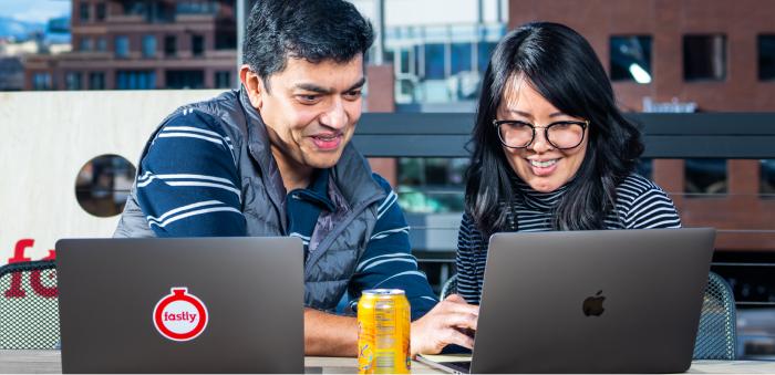Zwei Mitarbeiter von Fastly arbeiten über ihren Laptops auf einer Büroterrasse im Freien zusammen.