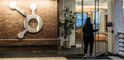 Eine HubSpot-Mitarbeiterin, die den Hauptsitz des Unternehmens in Cambridge, Massachusetts, betritt