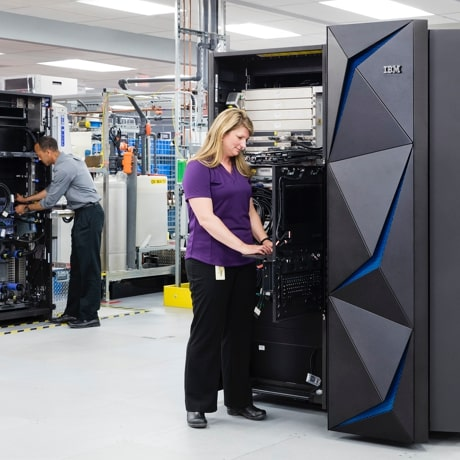Two employees working with IBM hardware cabinets