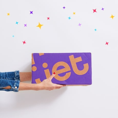 Two hands presenting a Jet delivery box below a pop of confetti
