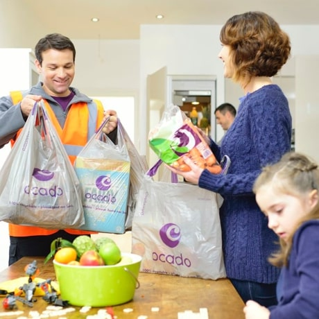 Ocado delivery driver handing over several bags full of food shopping