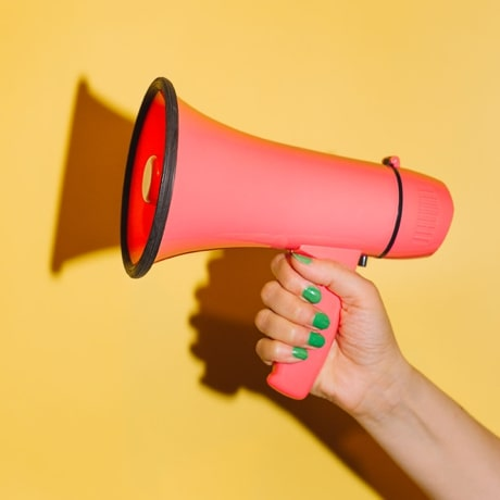 Hand holding a pink megaphone