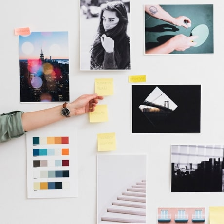 Le bras d'une personne qui colle un Post-it au mur, à côté d'autres Post-it et de photos