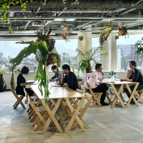 オープン型のオフィスのテーブルの周囲で働きながら話しあう従業員