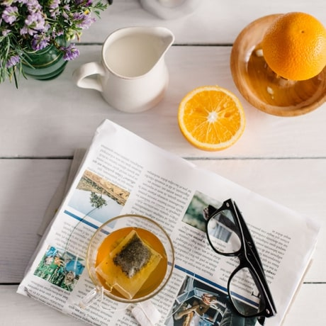 Table with a newspaper, cup of tea, reading glasses, and sliced orange