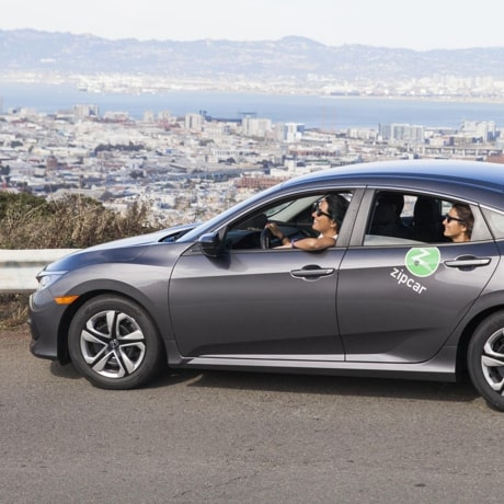 Friends in a Zipcar vehicle driving along a scenic road