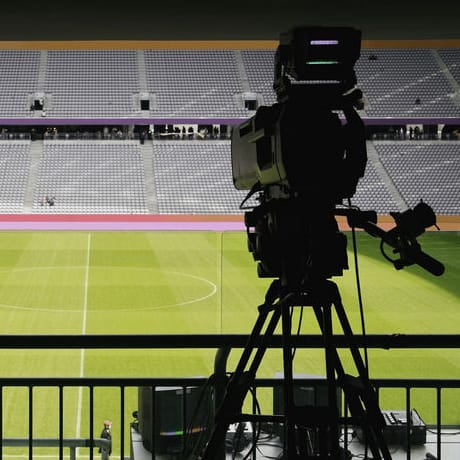 Television camera pointed towards the pitch in a soccer stadium