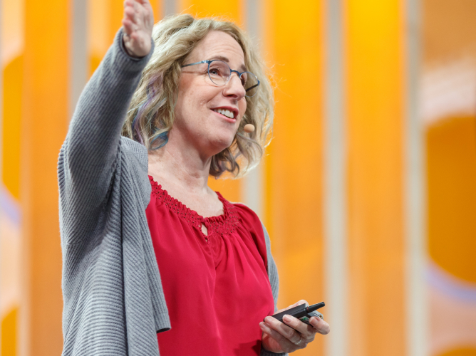 A speaker gestures as she delivers an energizing talk from the Slack Frontiers 2019 stage