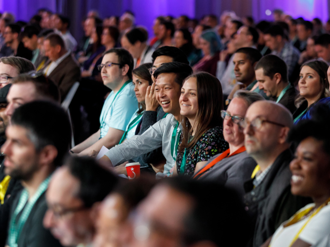 The diverse crowd at Slack Frontiers looks engaged and entertained as they listen to a keynote