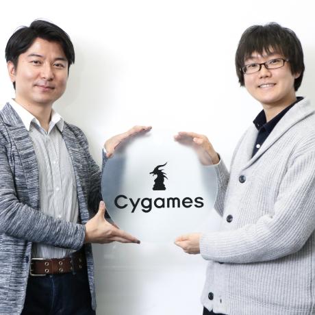 Cygames のロゴが刻まれた丸いガラスのサインプレートを挟んで微笑む二人の男性