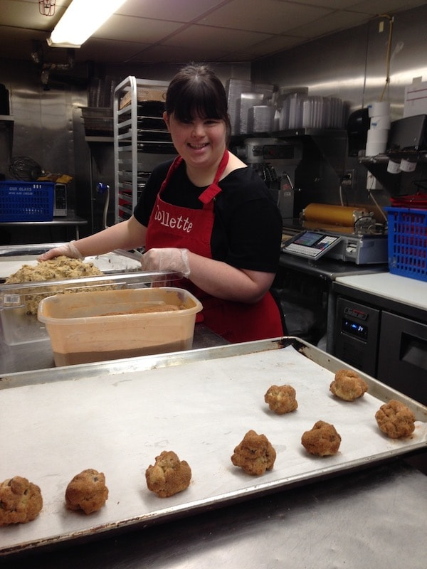 Collette bakes cookies in a kitchen wearing an apron with her name on it
