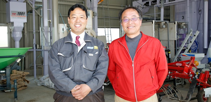 Two Kakuichi employees standing in an warehouse full of agricultural equipment