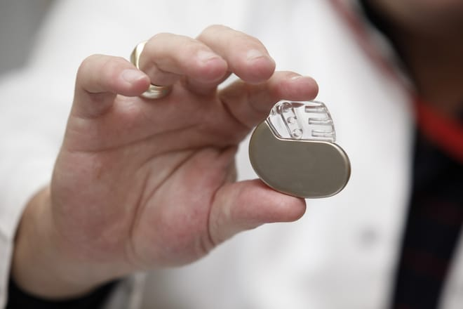 A doctor wolds a small pacemaker in her hand.