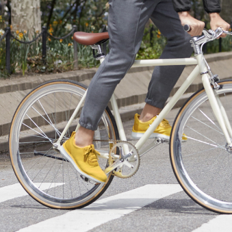 'A cyclist wears yellow Cole Haan sneakers while pedaling through a crosswalk.'