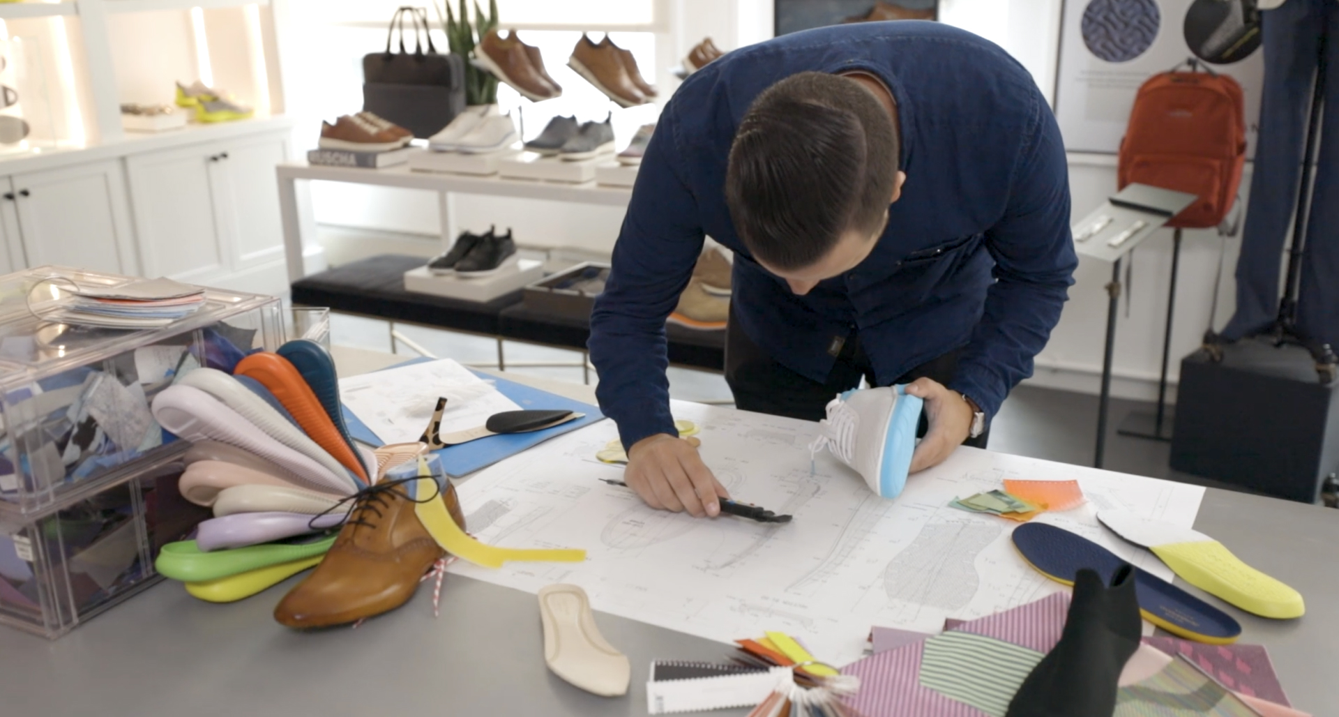 A Cole Haan designer studies the blueprint for a new shoe as part of a 15-month process that is coordinated through Slack.